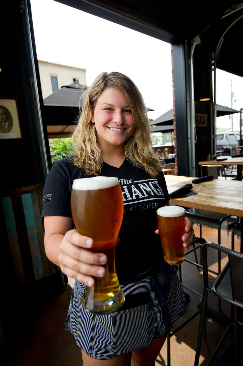 A server holds two beers to illustrate dinner and dining options in SoIN (southern Indiana).