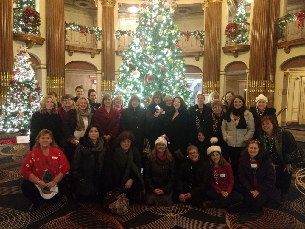 Travel group with holiday tree in background