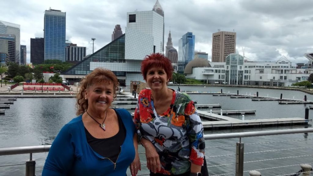 Discover My Cleveland owners with Cleveland skyline in background